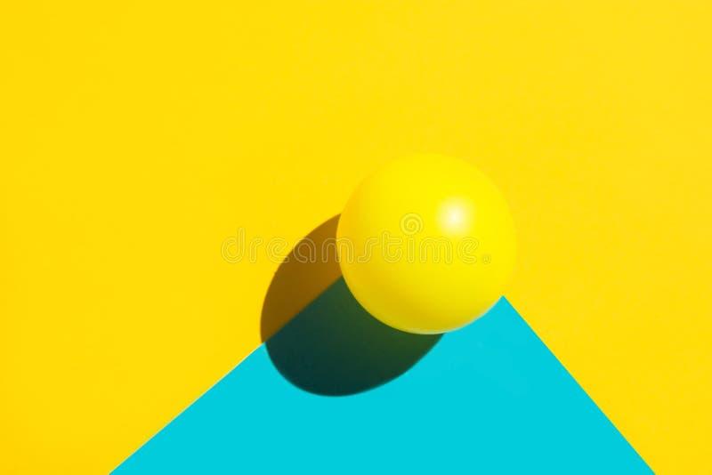 Bola de tênis amarela no elemento azul da forma do polígono do duotone Composição geométrica gráfica colorida do sumário fotografia de stock