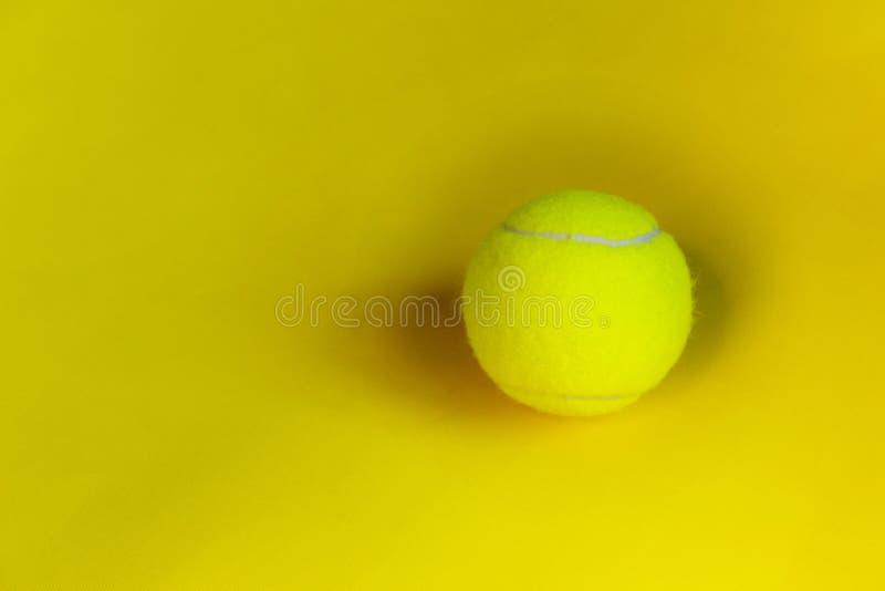 Bola de tênis amarela sobre o fundo amarelo Fundo abstrato do esporte imagem de stock royalty free