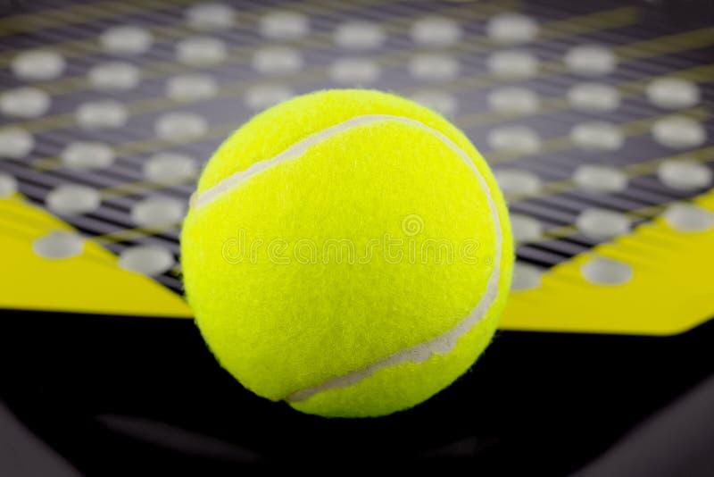 A bola de tênis encontra-se em uma raquete para jogar o tênis da praia foto de stock