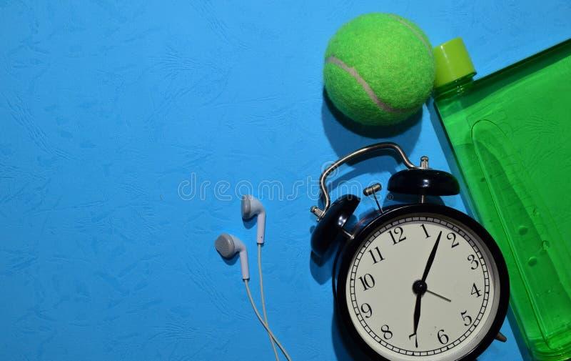 Bola de tênis, fone de ouvido, despertador verde e garrafa indicando o plano do exercício no fundo azul Conceito saudável e da ap imagem de stock royalty free