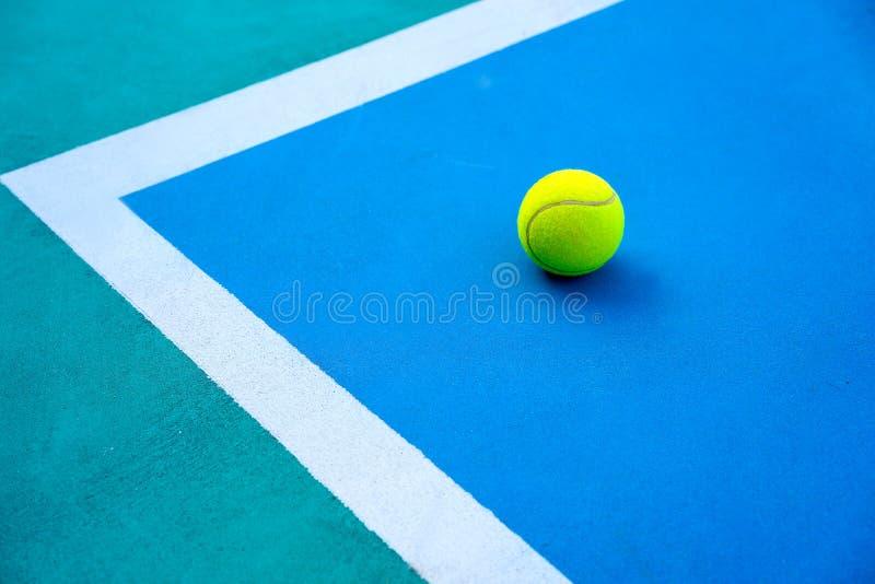 Bola de tênis na corte azul moderna dura perto da linha branca imagem de stock