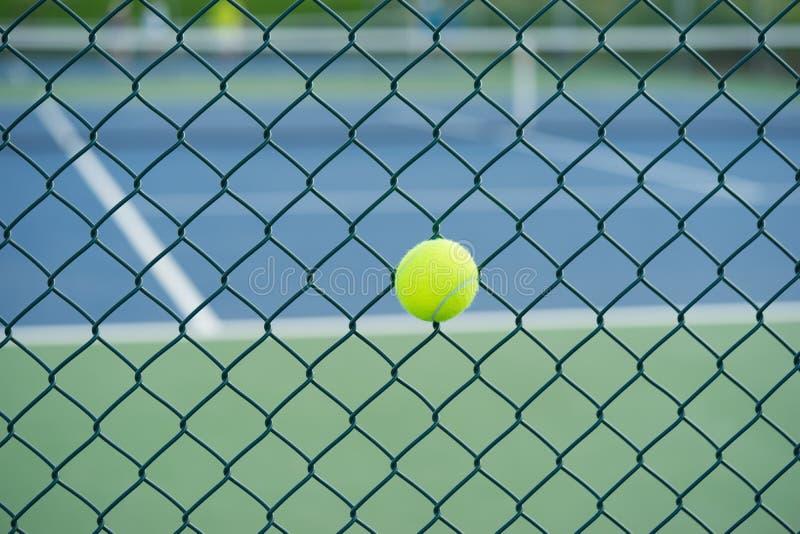 Bola de tênis no fio de metal contra o campo de tênis Conceito do equipamento da proteção do tênis fotos de stock royalty free