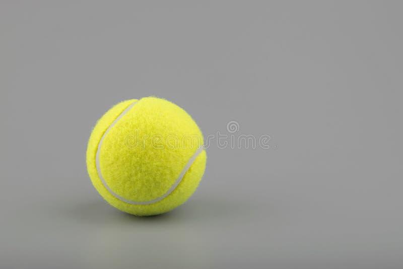 Bola de tênis no fundo cinzento fotos de stock