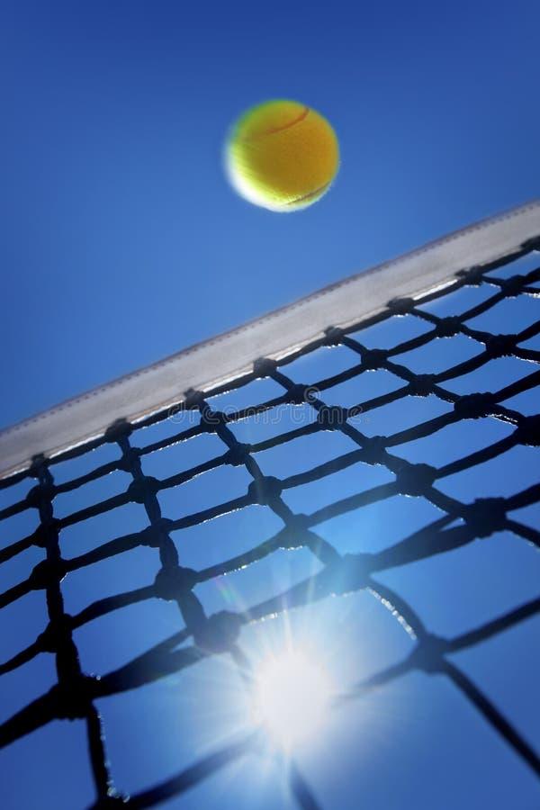 Bola de tênis sobre a rede fotografia de stock