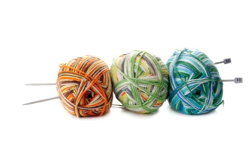 Bola de tres mezclas de lanas y de agujas que hacen punto en el backgro blanco fotografía de archivo libre de regalías