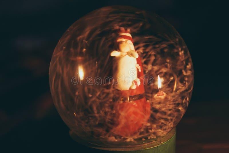 Bola de vidrio Nevado con el interior de Santa Claus, que refleja la vela ardiente imágenes de archivo libres de regalías