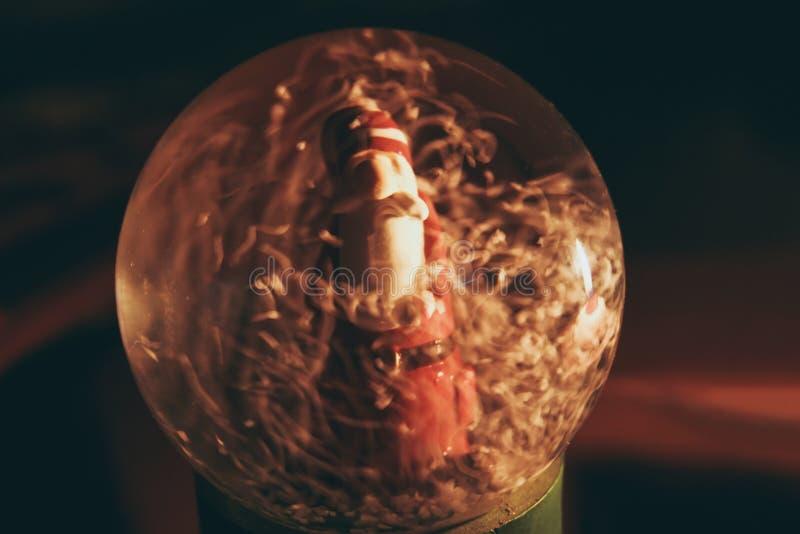 Bola de vidrio Nevado con el interior de Santa Claus, que refleja la vela ardiente fotografía de archivo