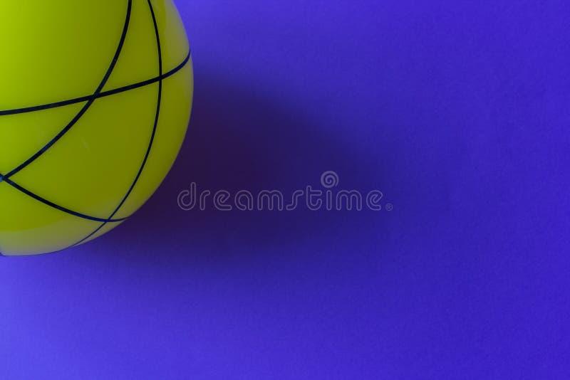 Bola de vidro amarela grande em um fundo azul Ainda vida de bola amarela listrada na tabela azul brilhante foto de stock royalty free