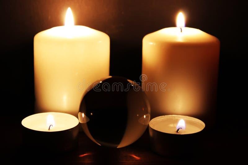 Bola de vidro e velas ardentes na obscuridade imagem de stock