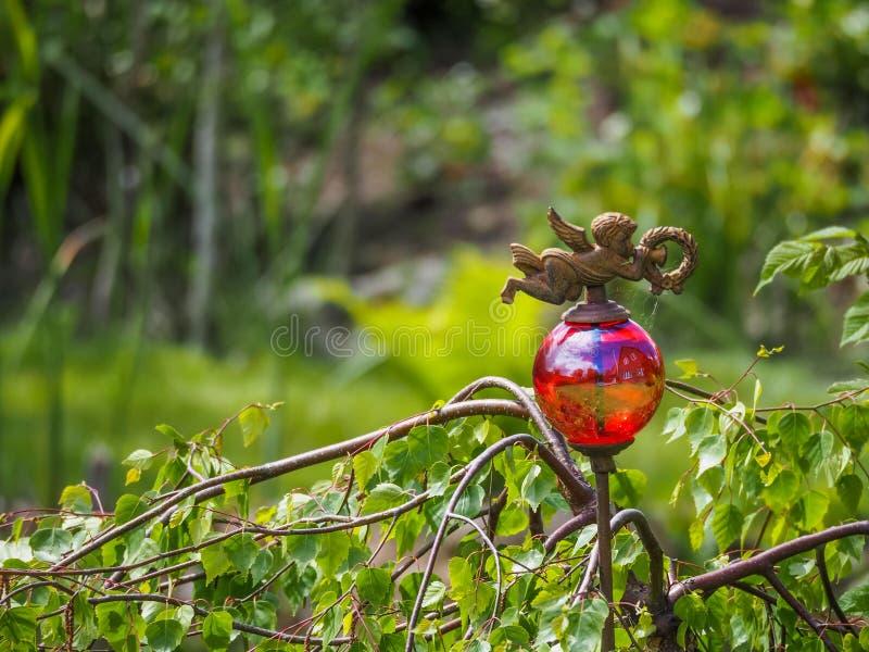 Bola de vidro transparente vermelha na vara oxidada com anjo e reflexão decorativos da casa, jardim em Alemanha fotografia de stock