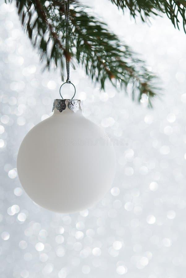 Bola decorativa branca na árvore do xmas no fundo do bokeh do brilho Cartão do Feliz Natal fotos de stock