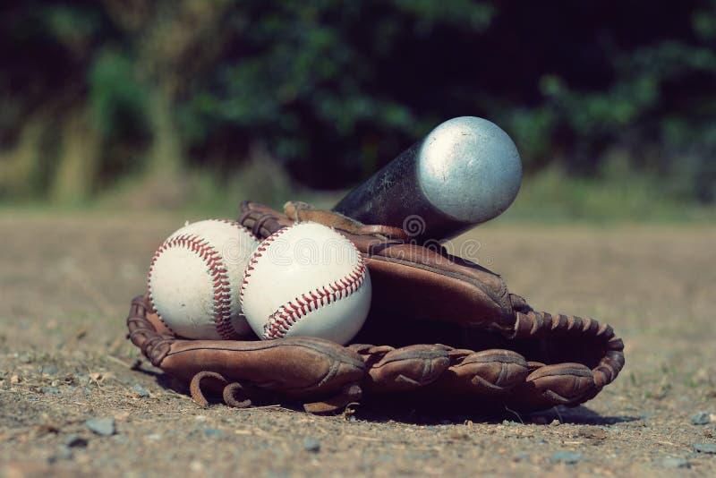 Bola del béisbol en el guante de cuero con un bate de béisbol que miente en el patio fotografía de archivo