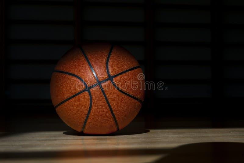 Bola del baloncesto en el entarimado con el fondo negro foto de archivo