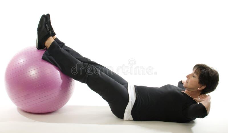 Bola del entrenamiento de la base del ejercicio de la aptitud de la mujer imagenes de archivo