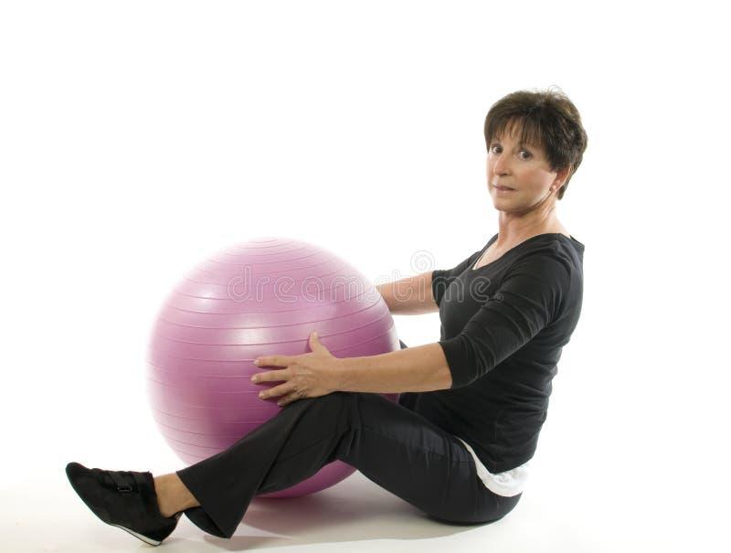 Bola del entrenamiento de la base del ejercicio de la mujer foto de archivo