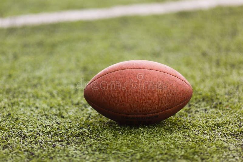 Bola del fútbol americano del rugbi que miente en el campo verde imagen de archivo