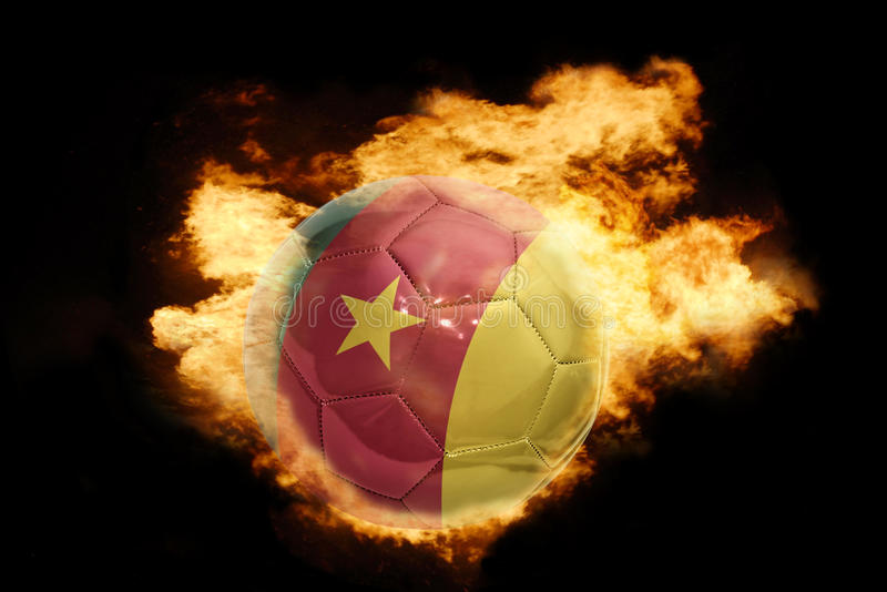 Bola del fútbol con la bandera del Camerún en el fuego imagen de archivo libre de regalías