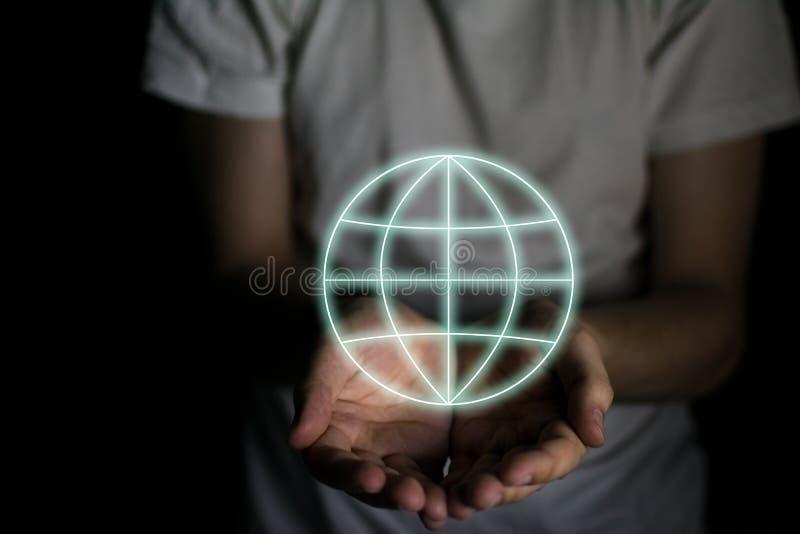 Bola del mundo entre las manos de un hombre en un fondo negro fotos de archivo libres de regalías