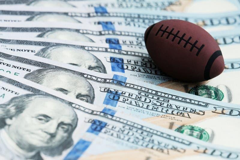 Bola del recuerdo para jugar a rugbi o a fútbol americano en billetes de banco de los E.E.U.U. El concepto de corrupción o de apu imagen de archivo libre de regalías