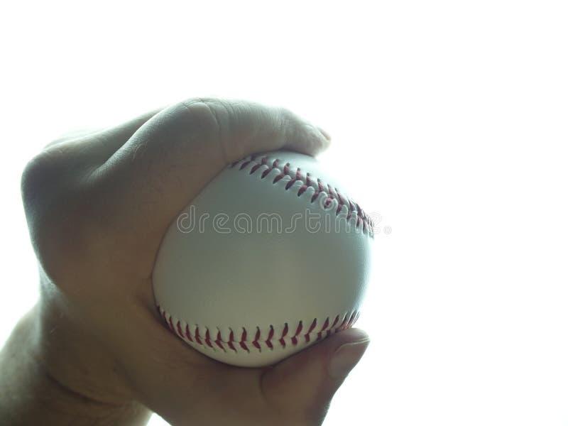 Bola do basebol na m?o masculina no fundo branco foto de stock