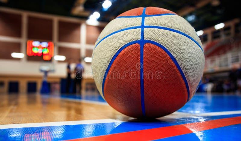Bola do basquetebol colocada no assoalho da corte Arena borrada com povos defocused foto de stock royalty free