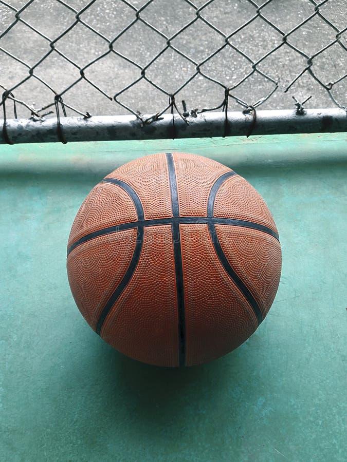 Bola do basquetebol sobre o assoalho no gym fotografia de stock