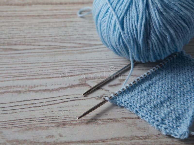Bola do fio e da confecção de malhas em uma tabela imagem de stock