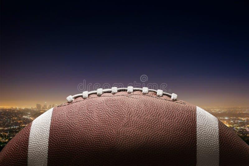 Bola do futebol americano no fundo da cidade fotografia de stock royalty free