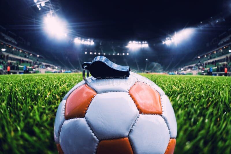 Bola do futebol com assobio na grama no estádio de futebol, vinta foto de stock royalty free