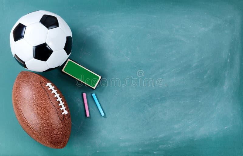 Bola do futebol e de futebol no quadro limpado com eliminador e giz foto de stock
