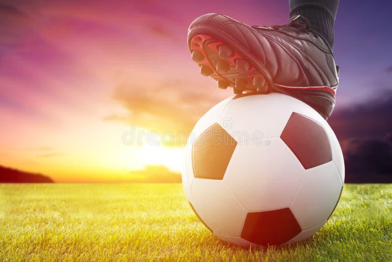 Bola do futebol ou de futebol no lance inicial de um jogo com por do sol imagem de stock