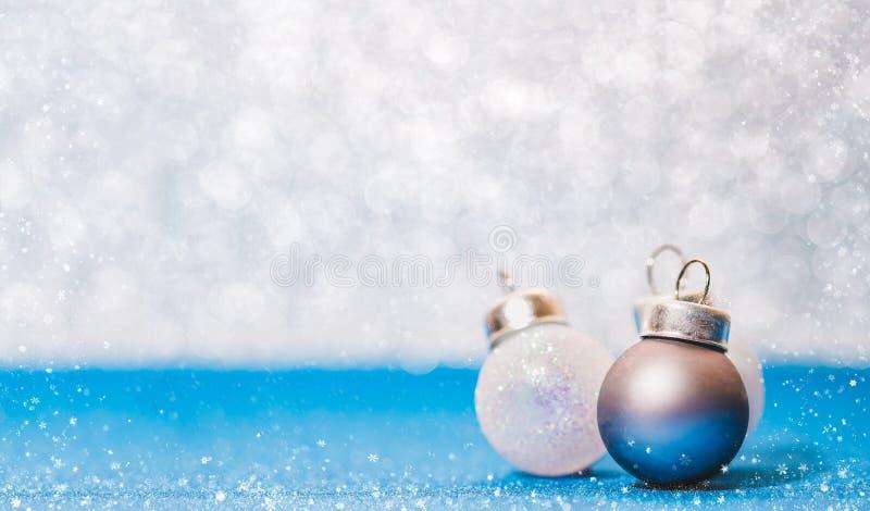 Bola do Natal no assoalho azul vívido do brilho e no borrão branco do bokeh imagens de stock royalty free