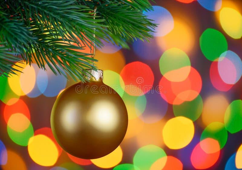 A bola do Natal no ramo do abeto no feriado ilumina o fundo fotos de stock royalty free