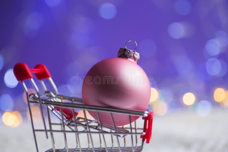 Bola do Natal do rosa do close up no trole do supermercado pequeno com luzes da festão no fundo roxo do bokeh fotos de stock royalty free