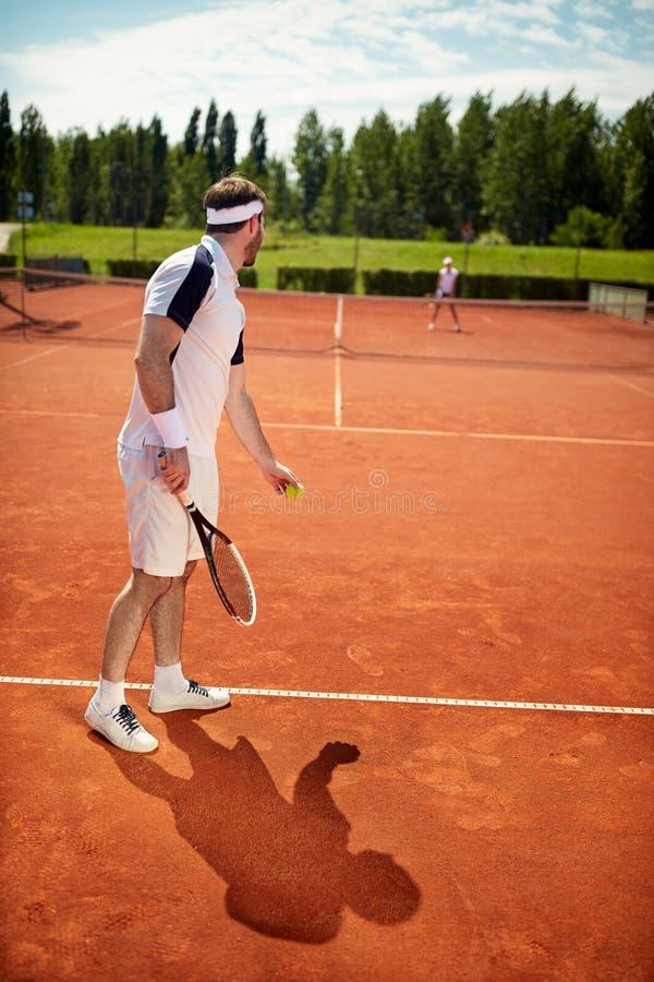 Bola do serviço do homem com a raquete no campo de tênis fotos de stock royalty free