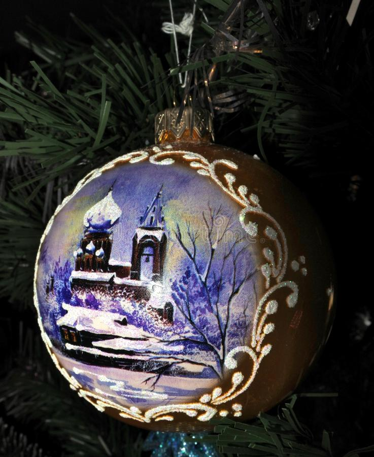 Bola dourada do brinquedo do Natal com uma imagem do inverno fotografia de stock