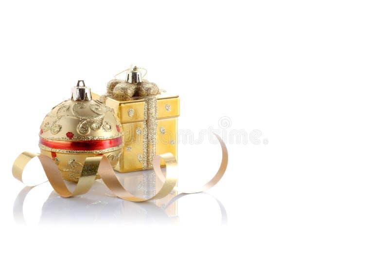 Bola dourada do Natal e um bloco pequeno para o presente isolado com espaço da cópia imagem de stock royalty free