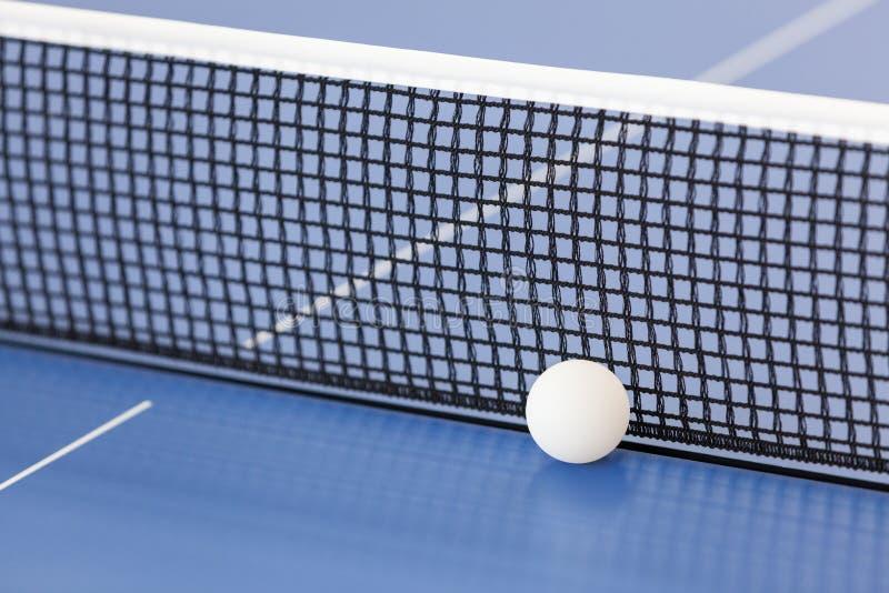 Bola e rede de tênis de mesa Sibile o azul de céu da esfera do pong da pá e do sibilo do tênis de Pong Conceito do esporte imagens de stock royalty free