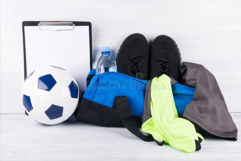 Bola e saco azul com coisas dos esportes para um treinamento do futebol em um fundo claro imagem de stock