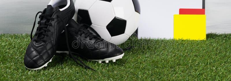 Bola e sapatas de couro para o futebol com um cartão do juiz na grama verde fotografia de stock royalty free