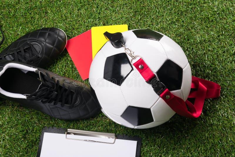 Bola e sapatas para o futebol com um assobio e violações do cartão para o juiz, na grama verde fotografia de stock royalty free