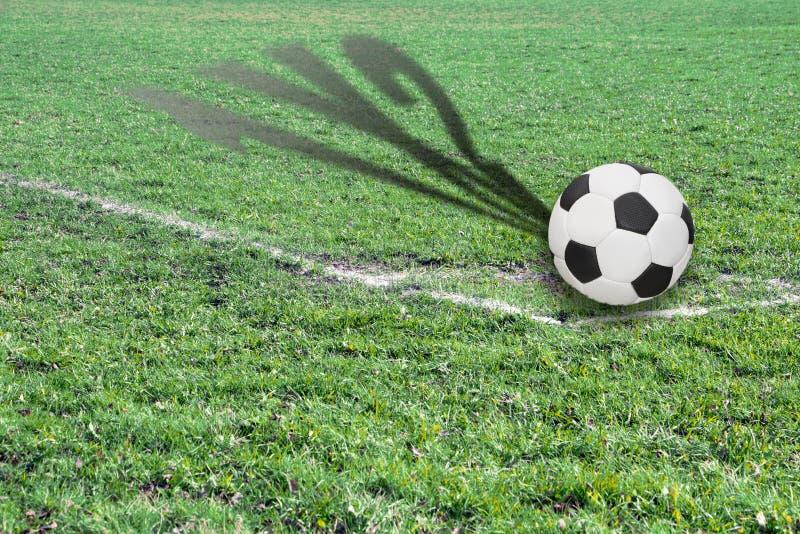Bola en un campo de fútbol con la sombra que muestra la cuenta posible fotos de archivo