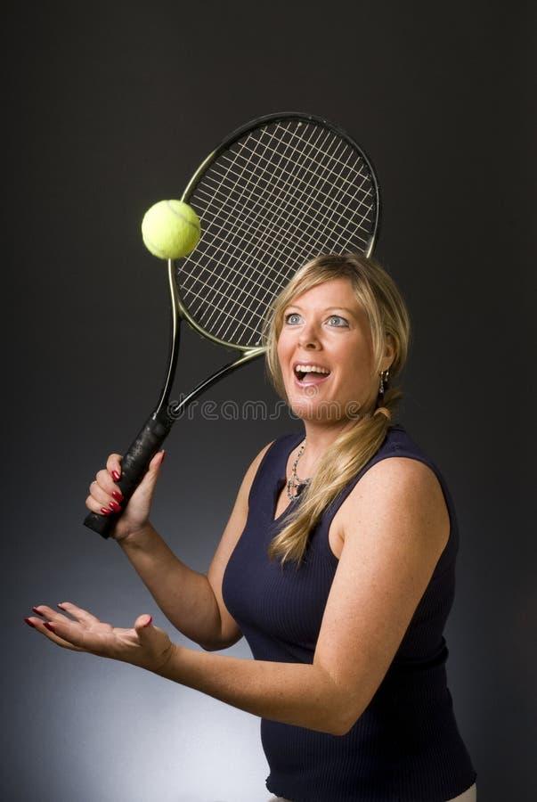 Bola feliz de la porción del jugador de tenis de la mujer imagen de archivo libre de regalías