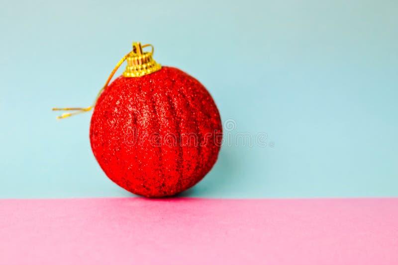 Bola festiva plástica de la Navidad de Navidad del pequeño vidrio redondo rojo, juguete de la Navidad enyesado sobre chispas en u imagen de archivo