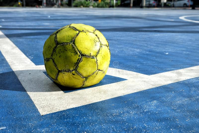 Bola futsal amarela velha na terra azul fotos de stock