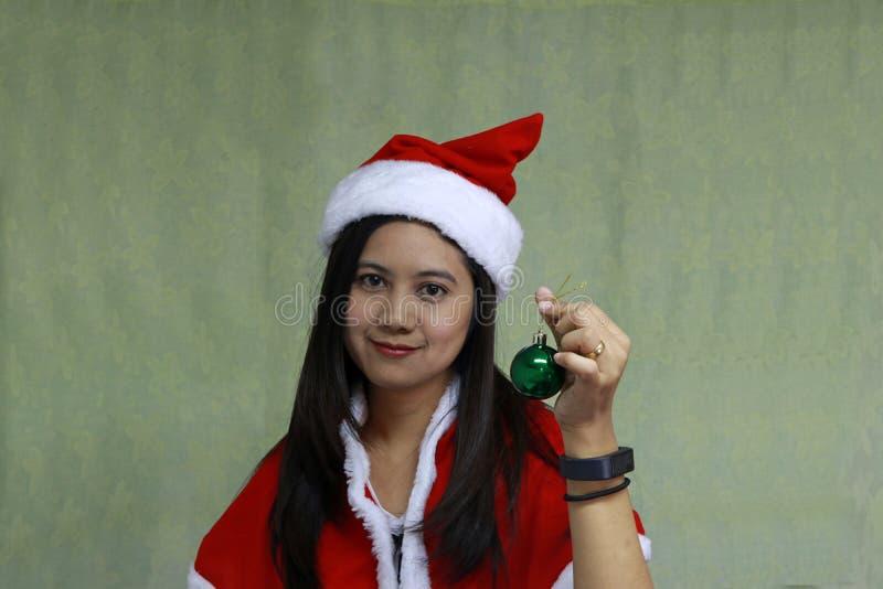 Bola mágica verde na mão do asiático Santa Girl Dress na luz - fundo verde fotografia de stock
