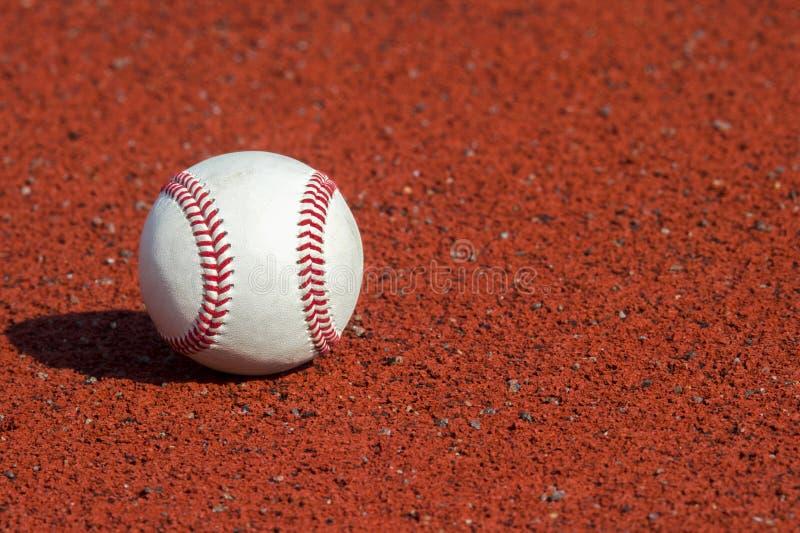 Bola nova do basebol na borracha vermelha da trilha foto de stock royalty free