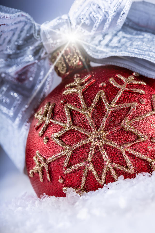Bola o vela roja de la Navidad con los ornamentos de oro, la cinta de plata y la nieve imágenes de archivo libres de regalías