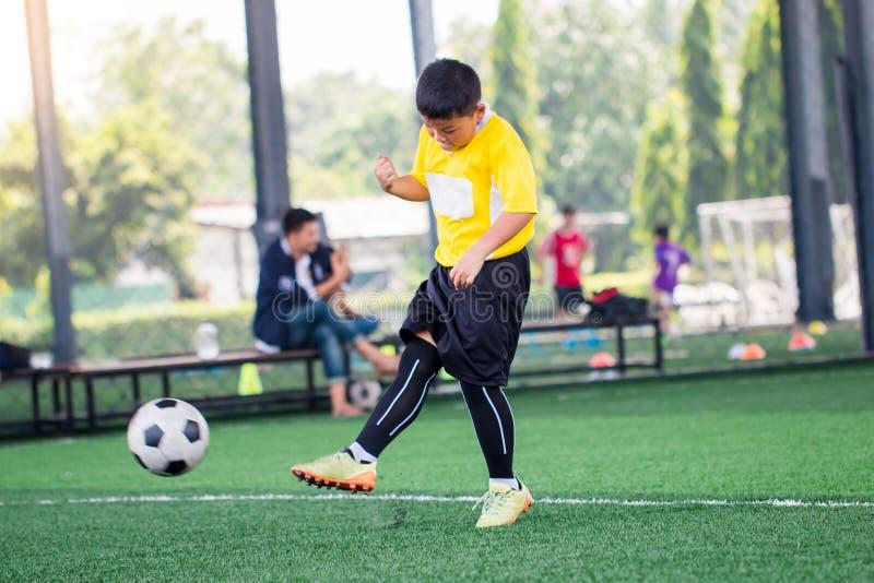 Bola obscura com a corrida asi?tica da velocidade do jogador de futebol da crian?a para disparar na bola ao objetivo no relvado a fotografia de stock