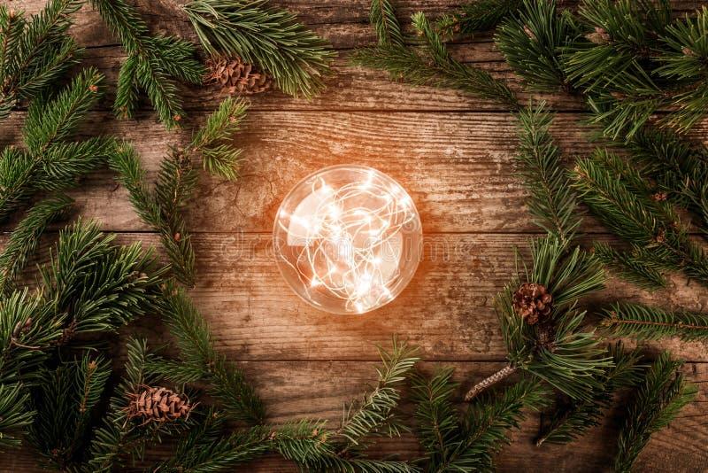 Bola que brilla intensamente de la Navidad en el fondo de madera con las ramas del abeto, picea, enebro, abeto, alerce, conos del fotografía de archivo
